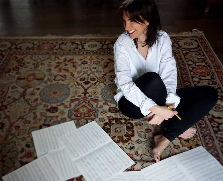 Composer Olivia Belli on the floor writing musical notations
