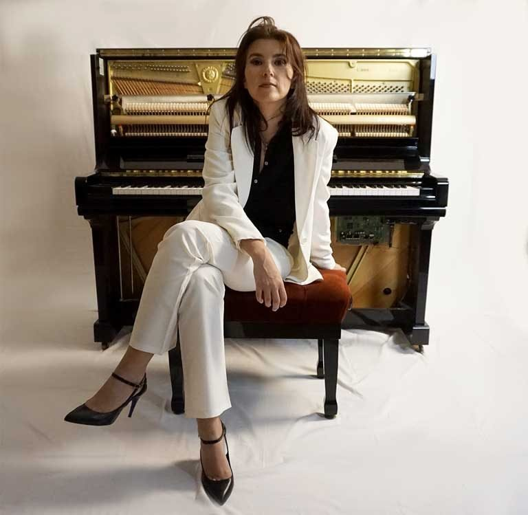 Composer Olivia Belli sitting in front of her piano